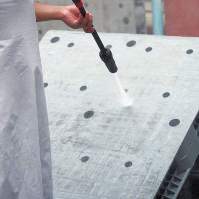 Worker pressure washing used stackable plastic pallets